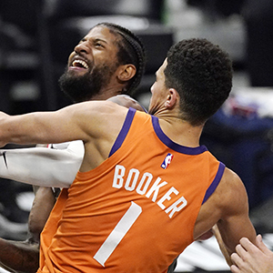 Phoenix Suns guard Devin Booker, right, blocks the shot of Los Angeles Clippers guard Paul George.